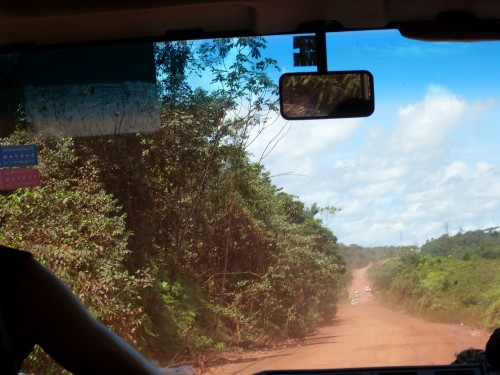 busje op rode weg Suriname