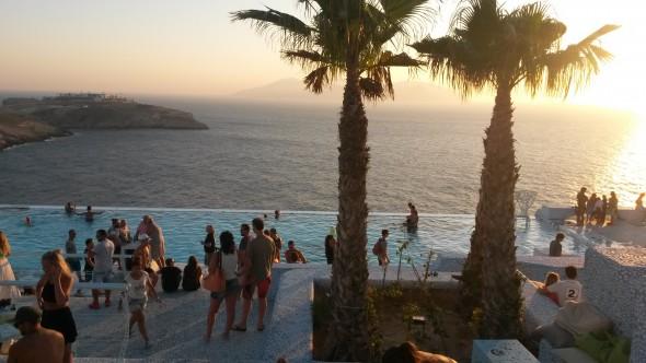 Vlak voor zonsondergang verzamelt iedereen zich rond de infinity pool, waar je zelfs kunst op de bodem ziet